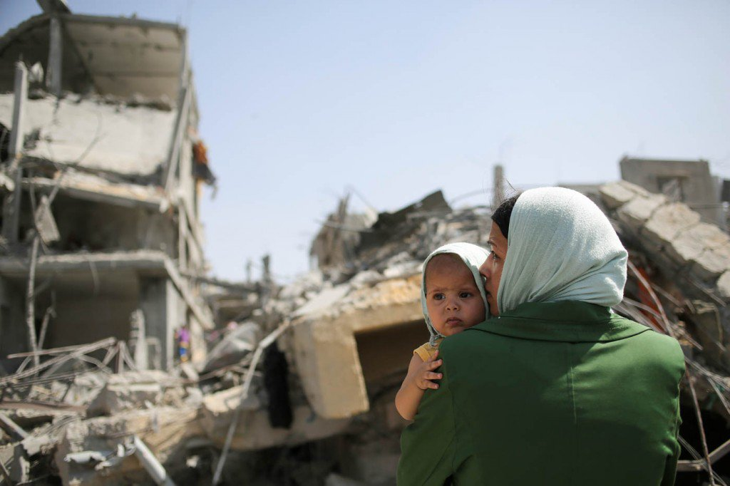 1-de-agosto-mulheres-palestinas-beijam-suas-crianças-na-frente-de-casas-destruídas-na-Faixa-de-Gaza-1024x682