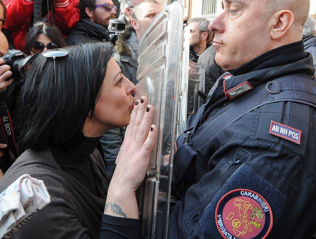 26-de-fevereiro-uma-mulher-beija-o-escudo-de-um-polocial-durante-a-visita-do-premier-italiano-Matteo-Renzi-em-Treviso-na-Itália-1024x774