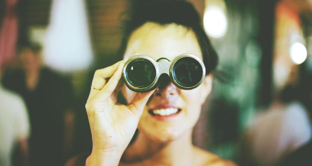Girl with binoculars looking into camera