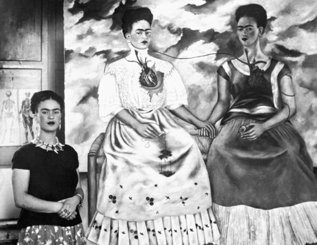 (Original Caption) Artist Frida Rivera Three Times. Spectacular sample of the distinctive art of Frida Kahlo Rivera, who has recently entered into a joint divorce agreement with her famous artist-husband, Diego Rivera, is this painting entitled, Me Twice. The artist stands at left. Painting shows the artist as [a] 19th Century lady, left, linked by blood vessels to the artist conceived as an Indian. October 24, 1939.